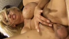 Blonde bimbo with a bad boob job gives her man a nice titty fuck